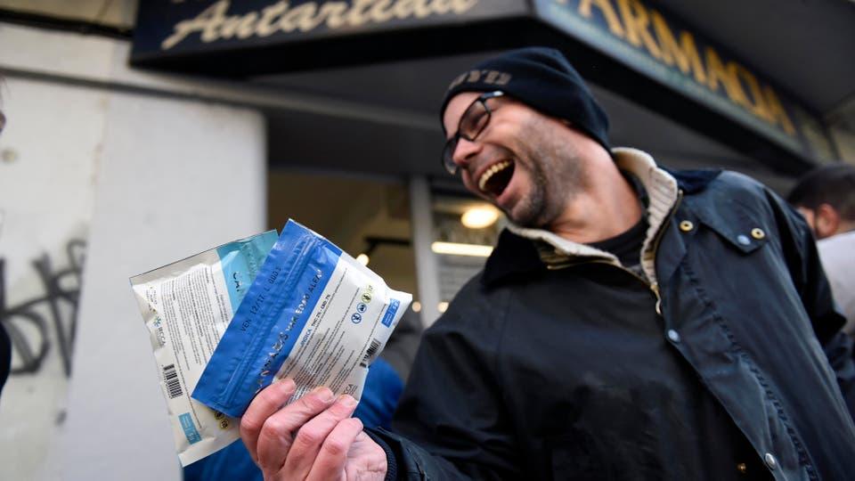 Un hombre muestra dos de los paquetes de marihuana legal frente a la farmacia Antártida en Montevideo. Foto: AP / Matilde Campodonico