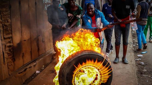 Partidarios del líder de la oposición, Raila Odinga, haciendo una barricada de llantas en Kibera, Nairobi