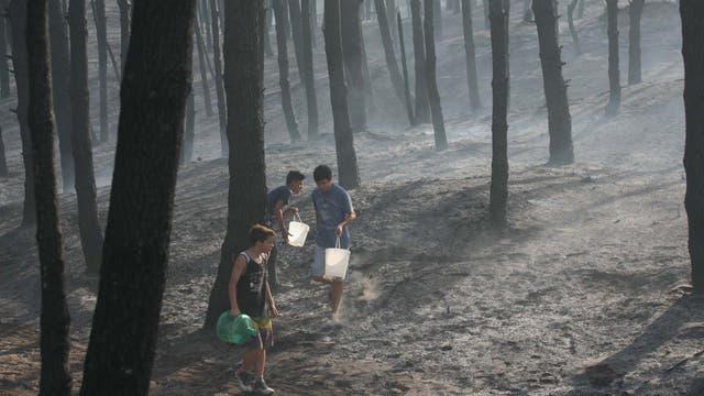 Una cadena humana de vecinos se pasan baldes de agua para apagar el fuego. Foto: LA NACION / Mauro V. Rizzi //Enviado especial