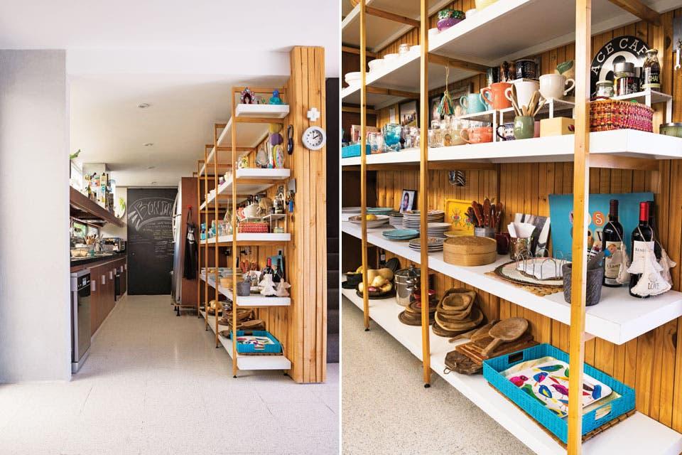 La espalda del muro de maderitas que remata el living da apoyo a un mueble de cinco metros de estantes continuos del lado de la cocina. Se optó por una mesada de granito negro absoluto que engama con las aberturas y se integra a la paleta de colores predominante.  Foto:Living /Celeste Najt