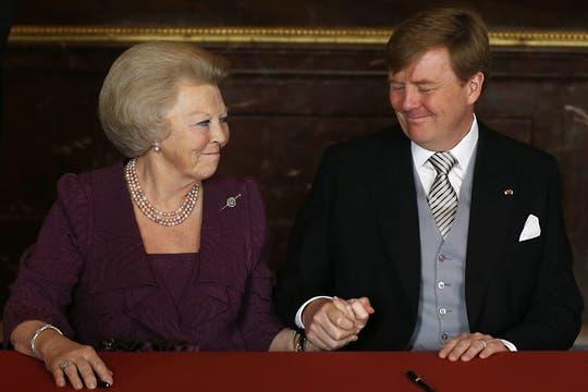 La reina Beatriz junto al príncipe Guillermo y a la princesa Máxima, firma la abdicación en favor de su hijo. Foto: AP