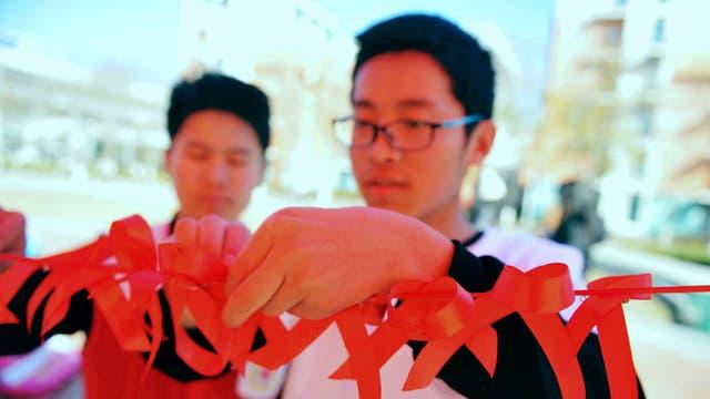 Estudiantes universitarios cuelgan cintas rojas para conmemorar el Día Mundial de la lucha contra el SIDA en Qingdao, en la provincia oriental de Shandong, China