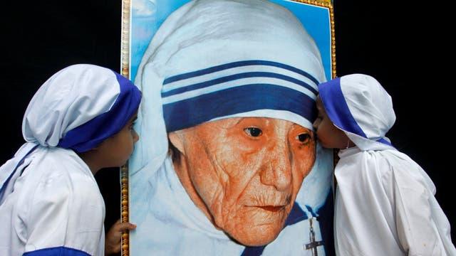 Dos niñas vestidas como Misioneras de la Caridad besan un retrato de la Madre Teresa de Calcuta durante una ceremonia en su honor en Bhopal (India), el de agosto de 2010