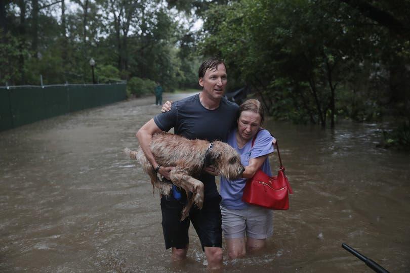Andrew White ayuda a una vecina después de rescatarla de su casa en su bote en el barrio River Oaks luego de las inundaciones. Foto: AFP