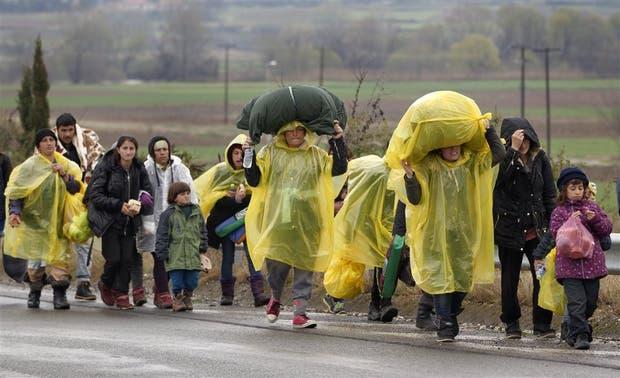 Un grupo de inmigrantes ilegales camina bajo la lluvia en Idomeni, en la frontera entre Grecia y Macedonia