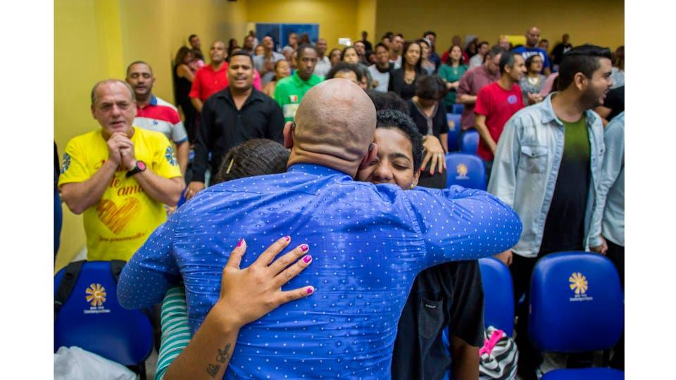 El Pastor Fabio de Souza abraza a la fiel Katia Maria Soares a su compañera Carolina y a su hijo durante el servicio dominical en la Iglesia Cristiana Contemporanea, la primera en el país en aceptar miembros de la comunidad LGBT, en Madureira, en Río de Janeiro