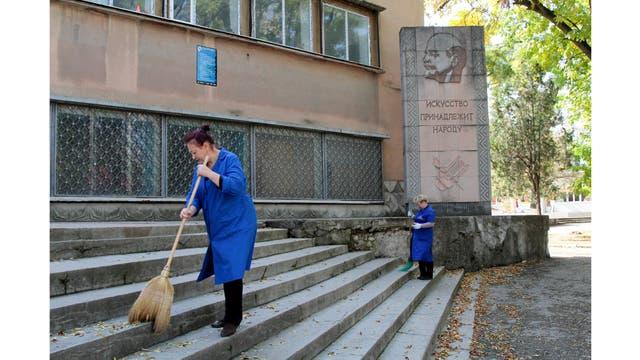 """Mujeres limpian junto a un monumento de Lenin con la inscripción debajo que dice: """"El arte pertenece a la gente"""", en Simferopol, Crimea"""