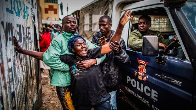 La madre de un hombre que recibió un disparo en la cabeza, supuestamente por la policía, junto a una furgoneta que transporta el cadáver de su hijo en Mathare, Nairobi