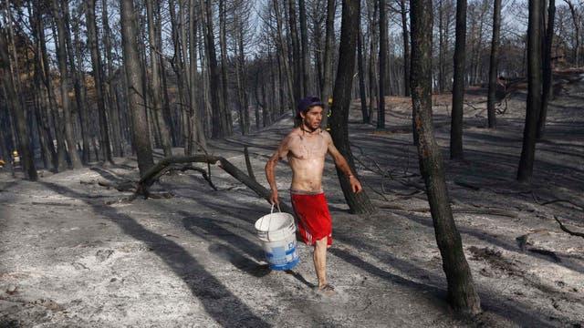Un joven corre con  balde de agua para sofocar las llamas. Foto: LA NACION / Mauro V. Rizzi //Enviado especial