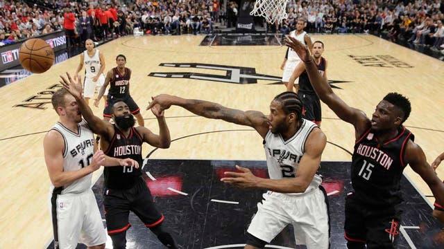 Kawhi Leonard pasa la pelota ante el acoso del jugador de Houston Rockets James Harden y su compañero David Lee