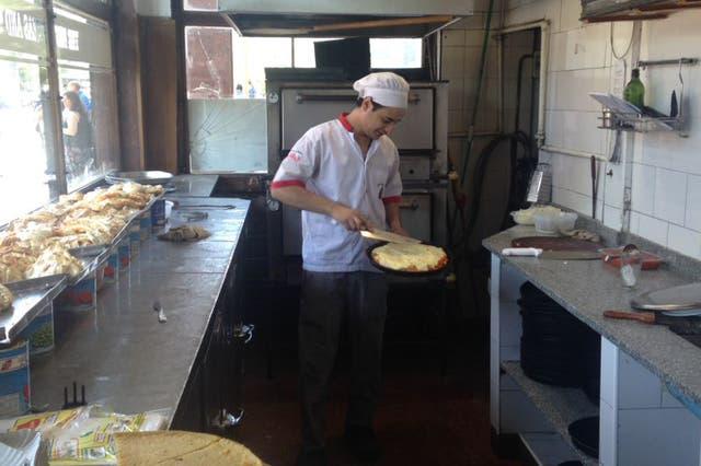 Hernán Castillo mete y saca pizzas del horno en pleno medio día