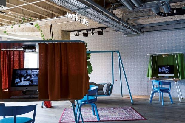 Caminando hacia el fondo, se llega al espacio que se ve sobre estas líneas, con islas de trabajo rodeadas de cortinas para darles privacidad y evitar reflejos sobre las pantallas. Entre ellas, sofá 'Swing' (Werner Aisslinger para Vitra).  Foto:Living /Daniel Karp