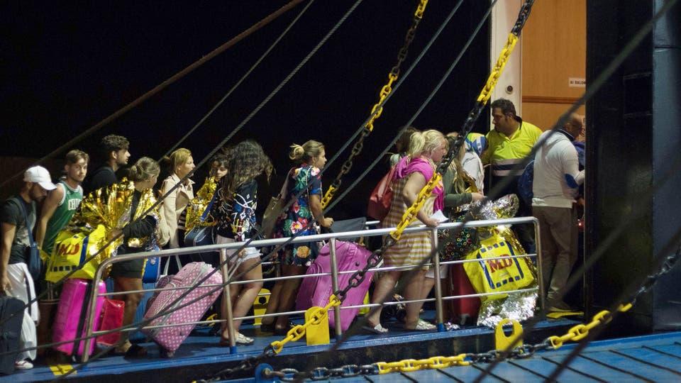 Muchos turistas abordan un barco luego del terremoto que sacudió a la isla. Foto: AFP