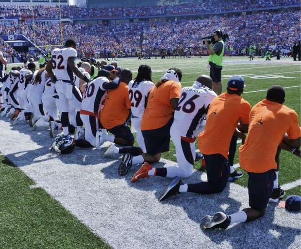 Integrantes de los Denver Broncos se arrodillaron anteayer durante el himno