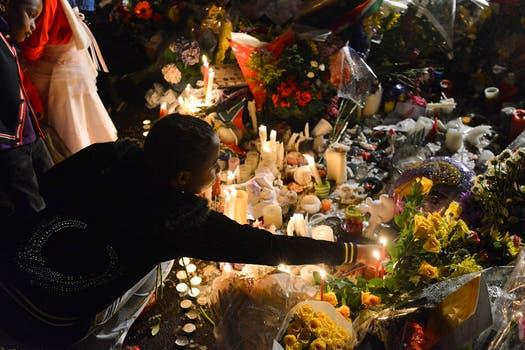 Una mujer enciende velas en honor a Mandela. Foto: Reuters