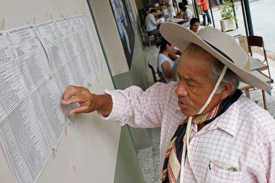 Félix Gauna busca en el censo electoral para la ubicación de su mesa de votación durante las elecciones generales en Santa Ana de los Guacaros, Argentina,. Foto: AP
