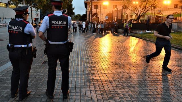 Dos policías catalanes vigilan la Escuela Francesc Macià, en Barcelona, mientras cientos de personas se agolpan para votar en el referéndum. Foto: Adrián Quiroga
