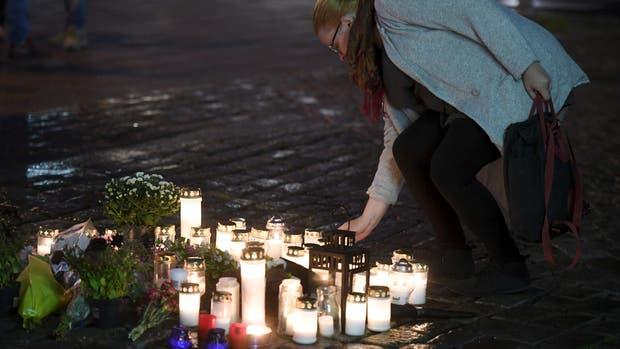 Una mujer deja una vela en un memorial para las víctimas, en Turku, Finlandia