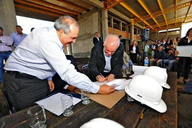 Lopez holds one of the plates while Morelli signs the contract in the middle of the terminal under construction
