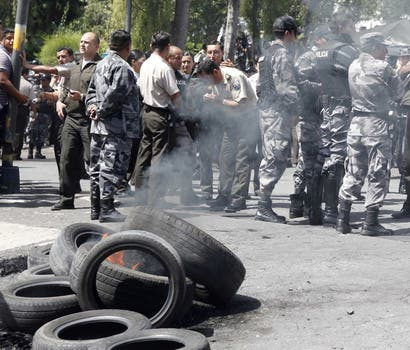 Oficiales de la policía ecuatoriana queman neumáticos durante la protesta por el recorte presupuestario. Foto: Reuters