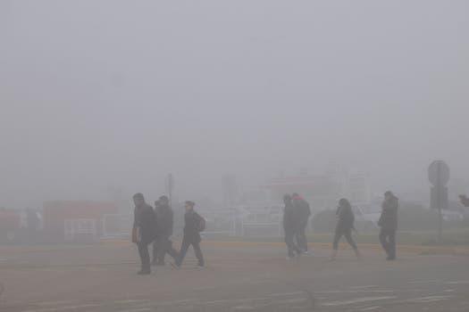 Varias personas caminan por el estacionamiento del aeropuerto de Ezeiza esperando que se normalicen los vuelos. Foto: DyN