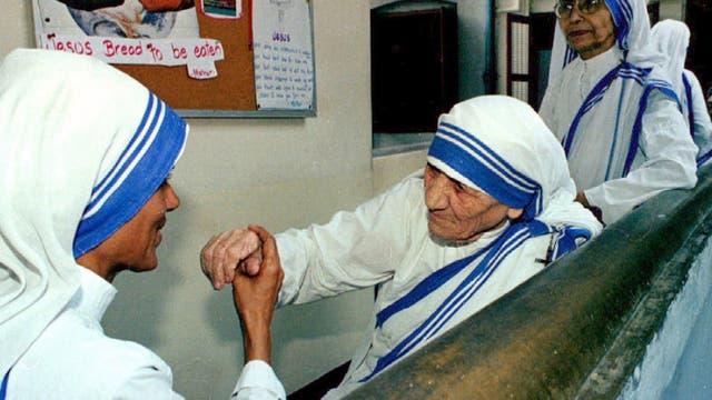Una de las hermanas misiones besa la mano de la Madre Teresa