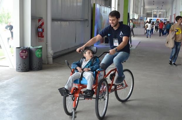 El creador de ErniBike, Diego Blas, da la primera vuelta en el rodado junto a Ernesto, el niño con discapacidad cerebral que la inspiró