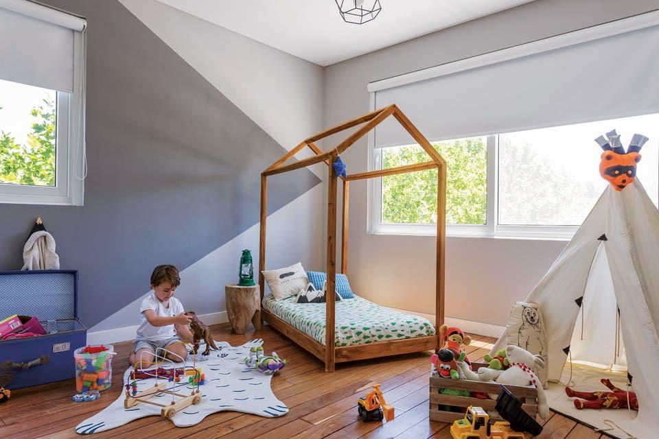 Cama de pino teñido (Lodd) con acolchado (Renata Home) y almohadón 'Montana' en lona estampada (Dod Kids). Como mesita, un tronco de madera (Mercado Libre) con un farol led irrompible de camping. Baúl forrado en tela (Ikea).  Foto:Living /Daniel Karp