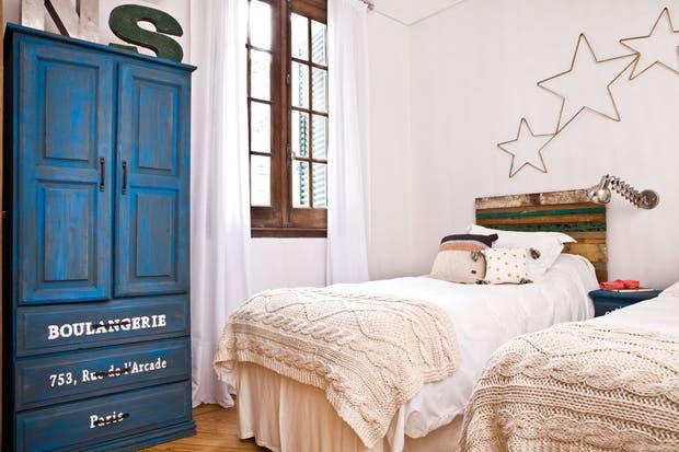 Se removió el barniz de las carpinterías de roble para resaltar su tono original. Se pintó íntegramente en blanco y se ambientó con muebles patinados y maderas de demolición. Ropero y mesa de luz patinados en azul, respaldos de cama de maderas recuperadas, pies tejidos en color crudo ($1.770, Cosa B.  /Santiago Ciuffo