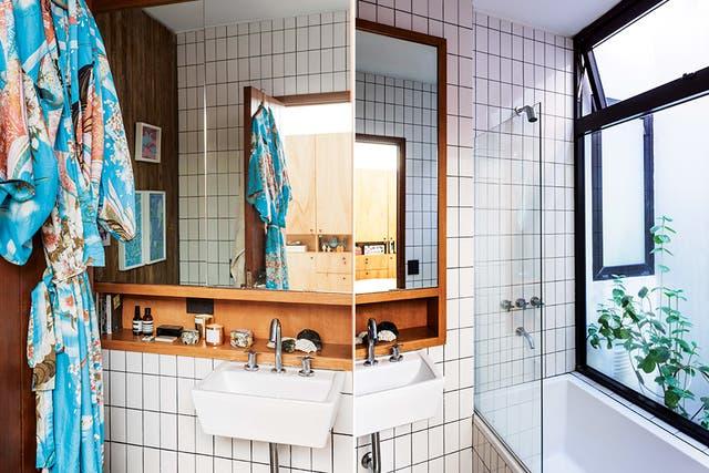 Los detalles en madera le dan carácter al baño, al igual que los azulejos tipo subway, pero orientados verticalmente y con juntas gruesas de pastina negra