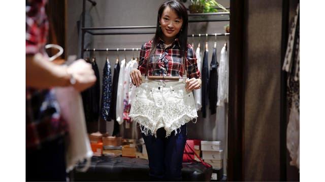 Eason Zhou, de 28 años, madre de un niño de 5 años, se anima a comprar pantalones cortos en una tienda de ropa en Shangai, luego de realizarse el tatuaje