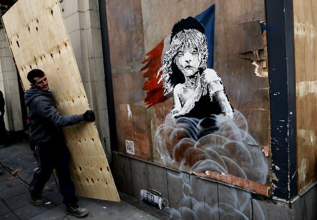 El mural del artista británico Banksy en un campamento de refugiados de Calais, en el momento que es tapado por las autoridades francesas