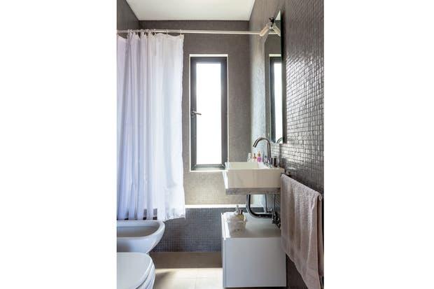Elegante y neto, en baño cuenta con venecitas grises de piso a techo y artefactos y cortina blanca.  /Daniel Karp