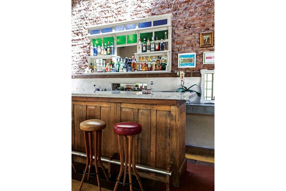 El bar, dispuesto a continuación del living, tiene el frente de una antigua pulpería de San Antonio de Areco, un mostrador de entrada de un petit hotel y banquetas con tapizado de cuero (Cueros Leather) a tono con el piso.  Foto:Living /Javier Picerno