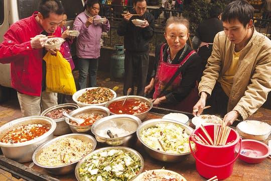 Distinto tiempo. Lo ancestral convive con el más vertiginoso presente. Arriba: a la izq., autopistas en Hangzhou; a la der., una degustación con toque occidental. Abajo: atardecer en un lago de esa misma localidad. Foto: Shutterstock