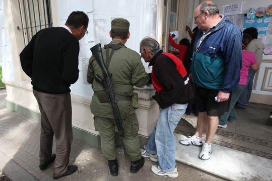 Un gendarem ayuda a varias personas a buscar su nombre en los padrones eletorales. Foto: LA NACION / Ricardo Pritupluk