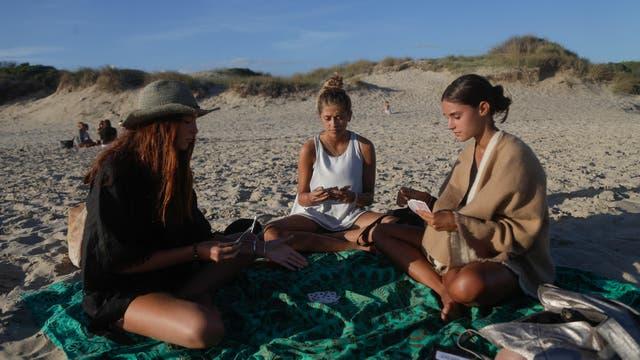 Las chicas juegan a las cartas en el sunset de La Mansa de José Ignacio