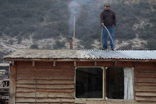 Un hombre limpia lla ceniza del techo de su casa en Bariloche. Foto: AP