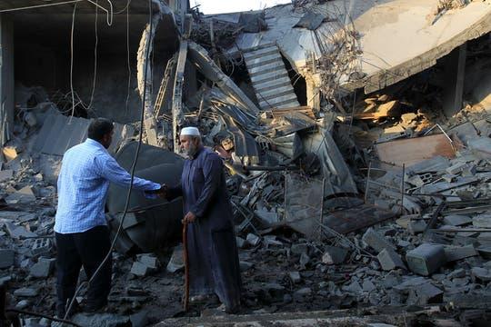 Palestinos pasan por delante de los escombros de una casa destruida tras un ataque aéreo israelí. Foto: AFP