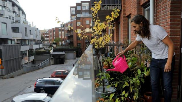 Daniel Jager riega las plantas en el balcón de su departamento en Estocolmo