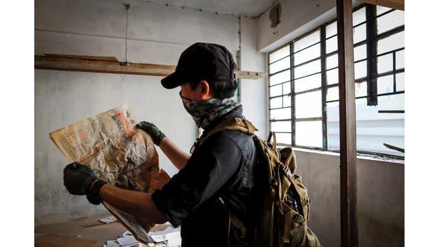 Un miembro de HK URBEX mira un diario de 1982 en el interior de un edificio residencial abandonado