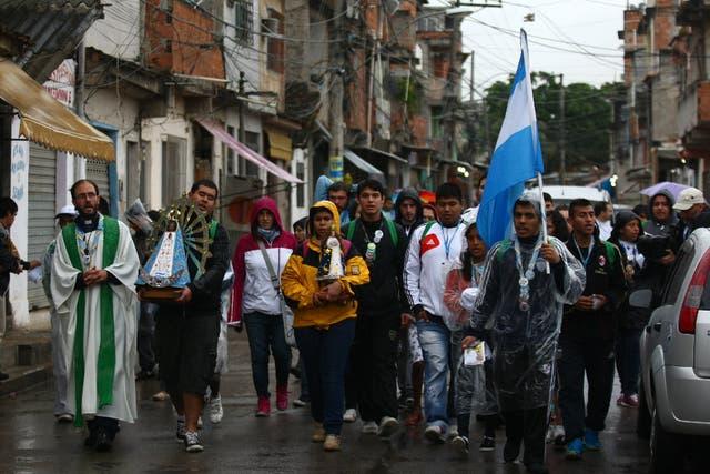 Un grupo de jóvenes de la villa 21 de Barracas llevan imágenes de las vírgenes de Lujan y de Caacupé a la favela de Varginha.
