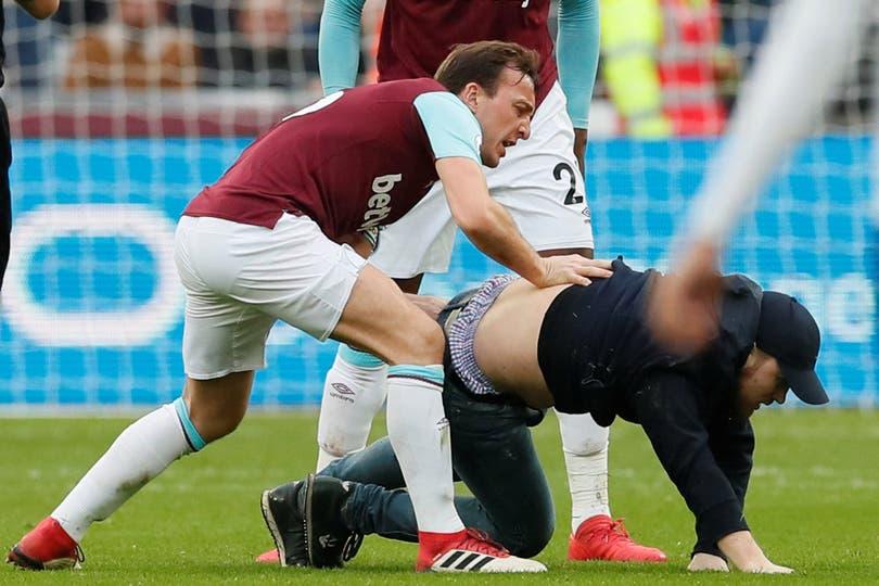 El jugador Mark Noble (West Ham) lucha contra uno de los que invadió el campo