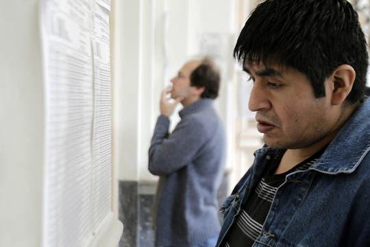 Dos hombres se buscan los padrones para poder votar. Foto: EFE