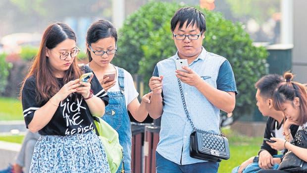 La vista en la pantalla y dedos rápidos mandando mensajes, una escena característica en un país con 1300 millones de usuarios de móviles