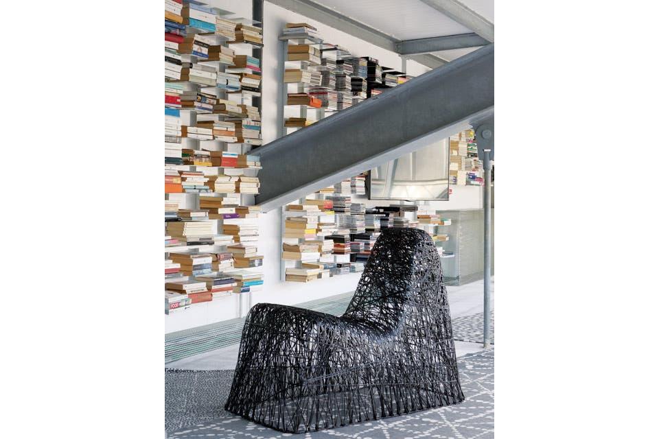 La escalera lleva a la biblioteca, con estantes de aluminio en los que los libros parecen flotar, donde se ubicó la tele.  /Enrico Conti