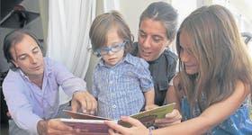La familia Campasso, se acomoda alrededor de Tomás (con Síndrome de Down), de 4 años, para disfrutar de un libro en la terraza de su casa