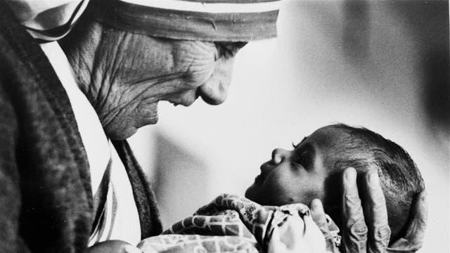 La Madre Teresa sostiene a una beba sin brazos en el orfanato de su Orden en Calcuta, en 1978