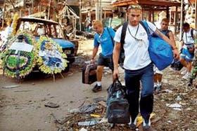 Un grupo de turistas extranjeros abandona el escenario del atentado, en Kuta Beach, Bali