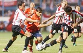 Agüero trata de pasar entre Juan Cáceres, Bastía y Fernando Ortiz; Bustos Montoya marcó para los Rojos e igualó Carrusca